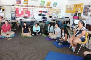 Caren McDonald sits with her high school students on the floor of her English classroom.