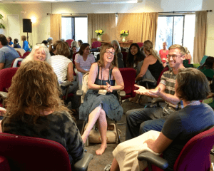 A circle of participants laugh and share ideas on the retreat.