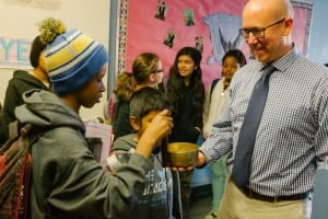 Brian Cooper stands in a school hallway and allows a student to ring his mindfulness bowl.