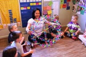Renee sits with children using a Hoberman sphere to breathe mindfully.