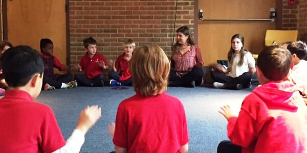 Cindy sits in a circle with students.